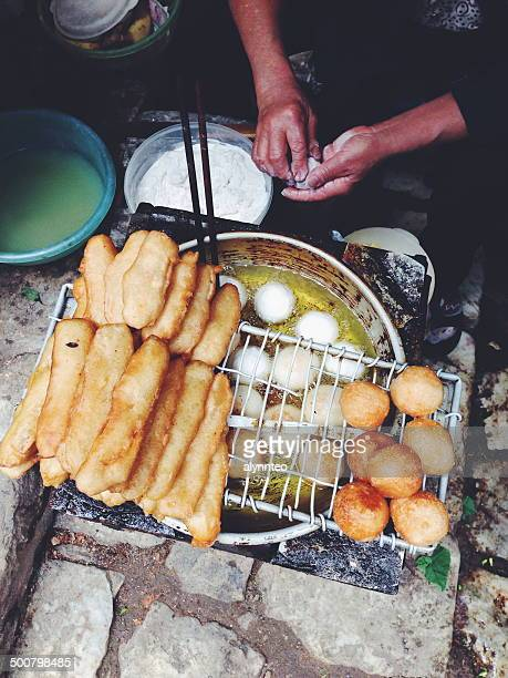 Vietnam, Lao Cai Province, Sa Pa, Woman frying dough on the street