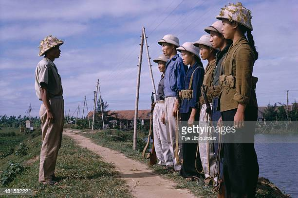 Vietnam North War Line of male and female Viet Cong soldiers standing in front of superior officer