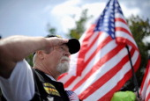 Vietnam veteran Jim Janeway salutes as 200 Vietnam POW's arrive at the Richard Nixon Presidential Library and Museum on May 23 2013 in Yorba Linda...