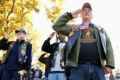 Vietnam War veteran Jim Hauser of Riva Maryland salutes with fellow veterans during a Veterans Day event at the Vietnam Veterans Memorial on the...