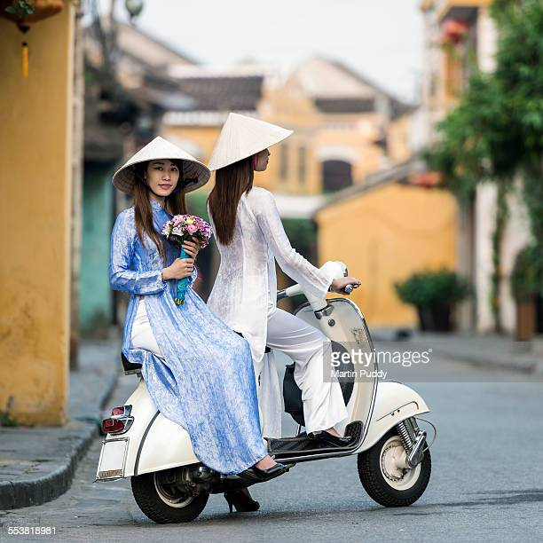 Vietnam, young women sitting on classic scooter