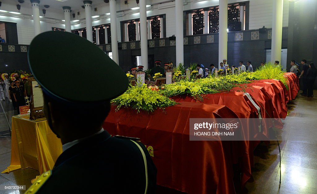 A Vietnamese Airforce soldier stands at attention next to the coffins of victims of a rescue aircraft that crashed on June 16, 2016 over the South China Sea during a search mission for a Vietnamese Airforce Sukhoi SU-30MK2 that went missing two days earlier, during an official funeral ceremony in Hanoi on June 30, 2016. / AFP / HOANG