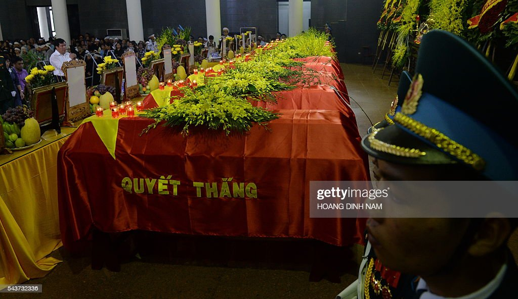 Vietnamese Airforce soldiers stand at attention next to the coffins of victims of a rescue aircraft that crashed on June 16, 2016 over the South China Sea during a search mission for a Vietnamese Airforce Sukhoi SU-30MK2 that went missing two days earlier, during an official funeral ceremony in Hanoi on June 30, 2016. / AFP / HOANG