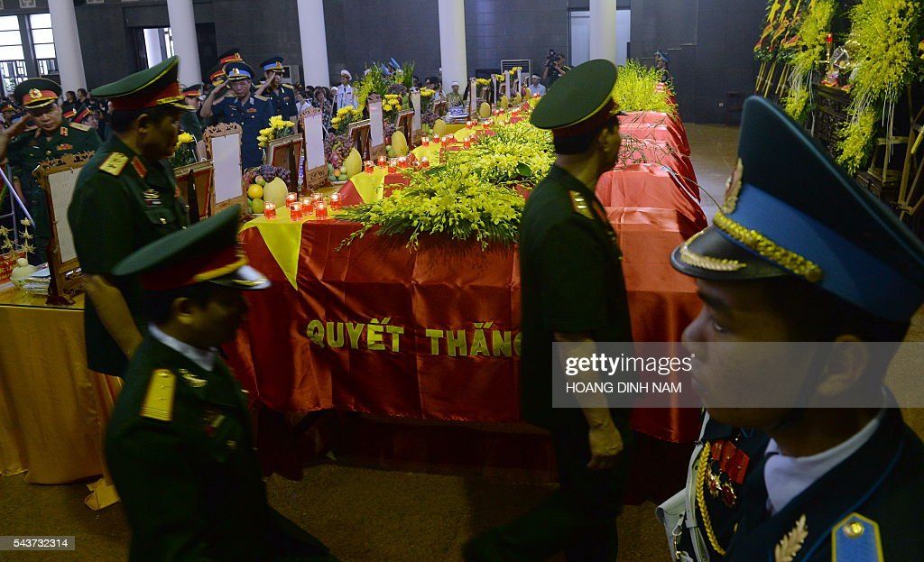 Vietnamese Army officers pay tribute to victims of a rescue aircraft that crashed on June 16, 2016 over the South China Sea during a search mission for a Vietnamese Airforce Sukhoi SU-30MK2 that went missing two days earlier, during an official funeral ceremony in Hanoi on June 30, 2016. / AFP / HOANG