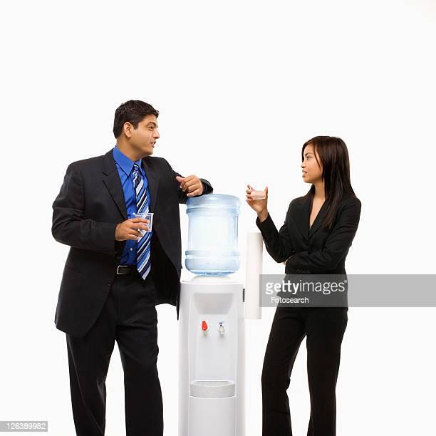 Vietnamese businesswoman and Indian businessman conversing at water cooler.