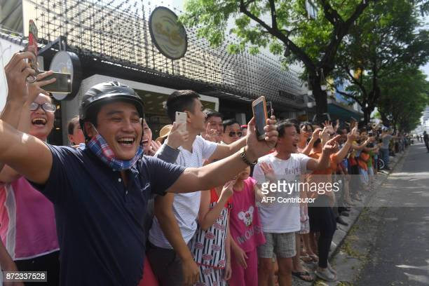 Vietnamese cheer as the convoy transporting US President Donald Trump passes by after his arrival for the AsiaPacific Economic Cooperation Summit in...