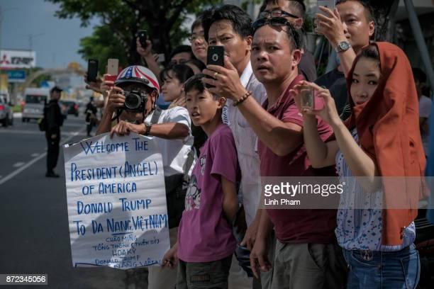 Vietnamese cheer as the convoy transporting US President Donald Trump passes by on Nguyen Van Linh Road on November 10 2017 in Danang Vietnam US...