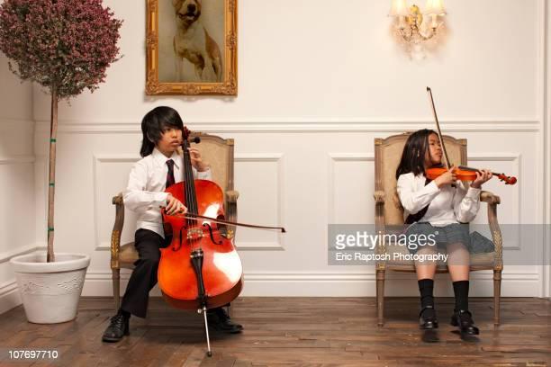 Vietnamese children with musical instruments sitting on elegant chairs