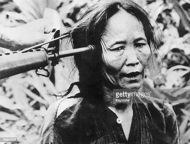 A Vietnamese civilian with a gun pointed at the side of her head