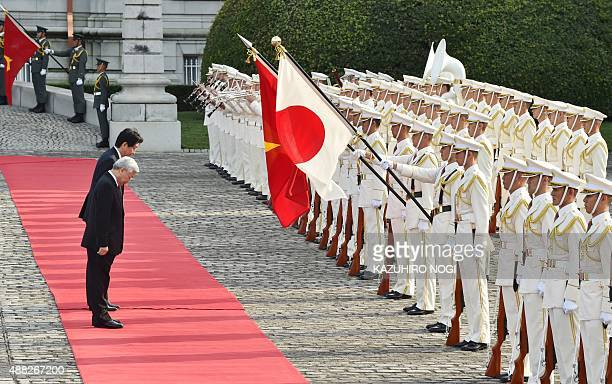 Vietnamese Communist Party General Secretary Nguyen Phu Trong is accompanied by Japan's Prime Minister Shinzo Abe as they review an honor guard...