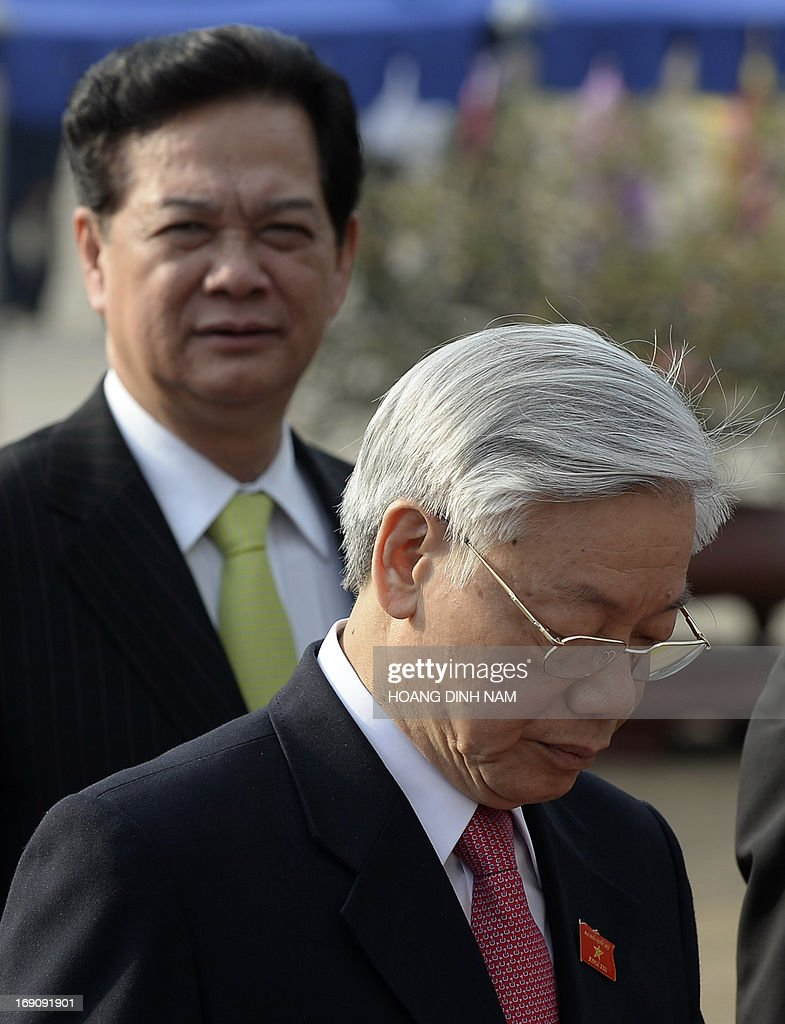 Vietnamese Communist Party Secretary General Nguyen Phu Trong (R) walks before Prime Minister Nguyen Tan Dung as they wait to pay hommage to late president Ho Chi Minh, at his mausoleum prior to the opening of the one-month-long summer session of the National Assembly in Hanoi on May 20, 2013 . AFP PHOTO/HOANG DINH Nam