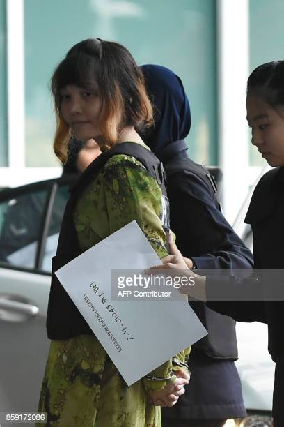 Vietnamese defendant Doan Thi Huong is escorted by police personnel as she arrives at the Malaysian Chemistry Department in Petaling Jaya outside...
