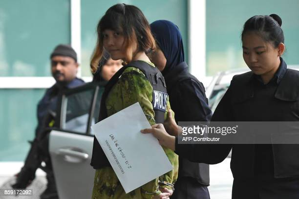 Vietnamese defendant Doan Thi Huong is escorted by police personnel following her arrival at the Malaysian Chemistry Department in Petaling Jaya...