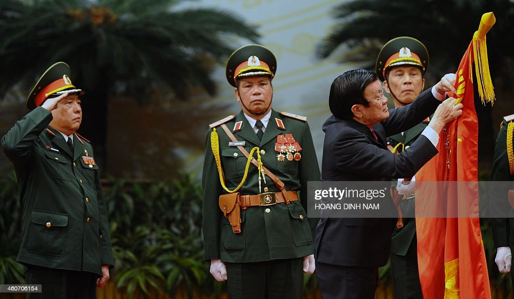 Vietnamese Defense Minister, Phung Quang Thanh (R) and his deputies greet Vietnamese President Truong Tan Sang (C) and Vietnam Communist Party Secretary General Nguyen Phu Trong (3rd L) during an official meeting marking the 70th anniversary of the Vietnam People's Army at the National Convention Center in Hanoi on December 20, 2014. The Vietnam People's Army (VPA) was founded on December 22, 1944.AFP PHOTO / HOANG DINH Nam