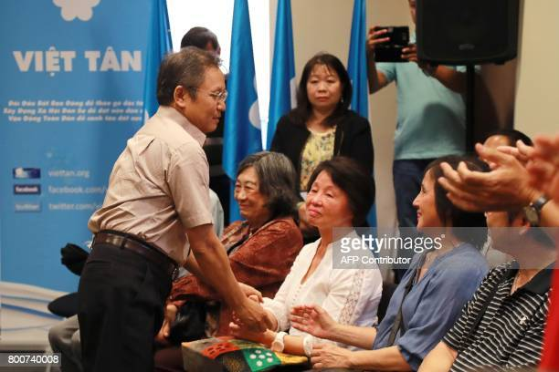 Vietnamese dissident blogger with dual French citizenship Pham Minh Hoang salutes people during a community meeting on June 25 2017 in an hotel of...