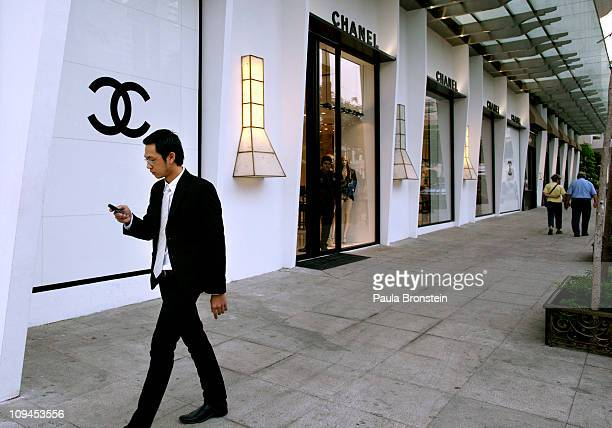 Vietnamese employee working at a luxury shopping center checks his phone as he leaves for lunch February 22 2011 in Ho Chi Minh City Vietnam Over the...