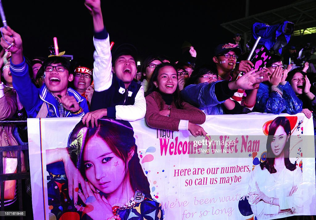 Vietnamese fans hold posters with names or portraits of SKorean K-pop bands or singers prior to a concert held at Hanoi's My Dinh stadium on November 29, 2012. Seventeen SKorean pop bands performed at the concert held to mark the 20th anniversary of the establishment of diplomatic ties between South Korea and Vietnam. AFP PHOTO/HOANG DINH Nam