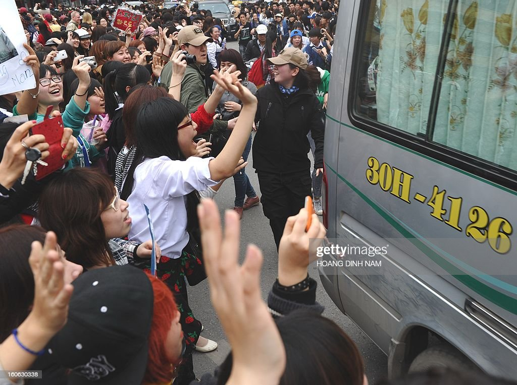 Vietnamese fans look towards a van carrying unidentified South Korean stars as they arrive to film a popular reality TV show 'Running Man'in downtown Hanoi on February 4, 2013. Stars including Song Ji Hyo, Hye Jin, Haha, Jong Kook, Lee Dong Wooka were amongst the personalities to attend the filming. AFP PHOTO/HOANG DINH Nam