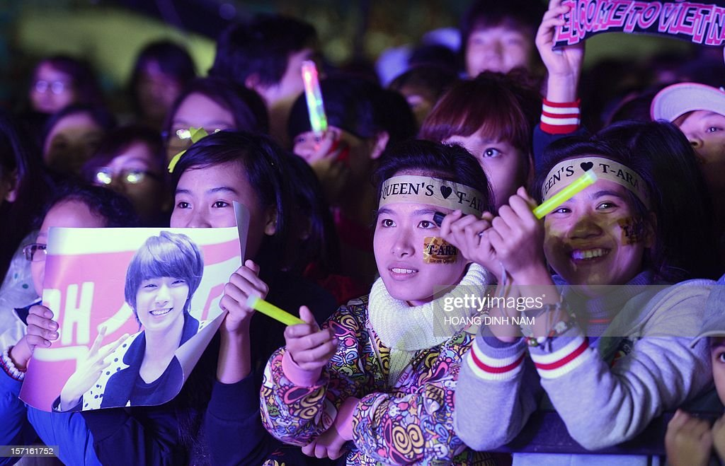 Vietnamese fans watch SKorean K-pop bands performing during a concert held at Hanoi's My Dinh stadium on November 29, 2012. Seventeen SKorean pop bands performed at the concert held to mark the 20th anniversary of the establishment of diplomatic ties between South Korea and Vietnam. AFP PHOTO/HOANG DINH Nam