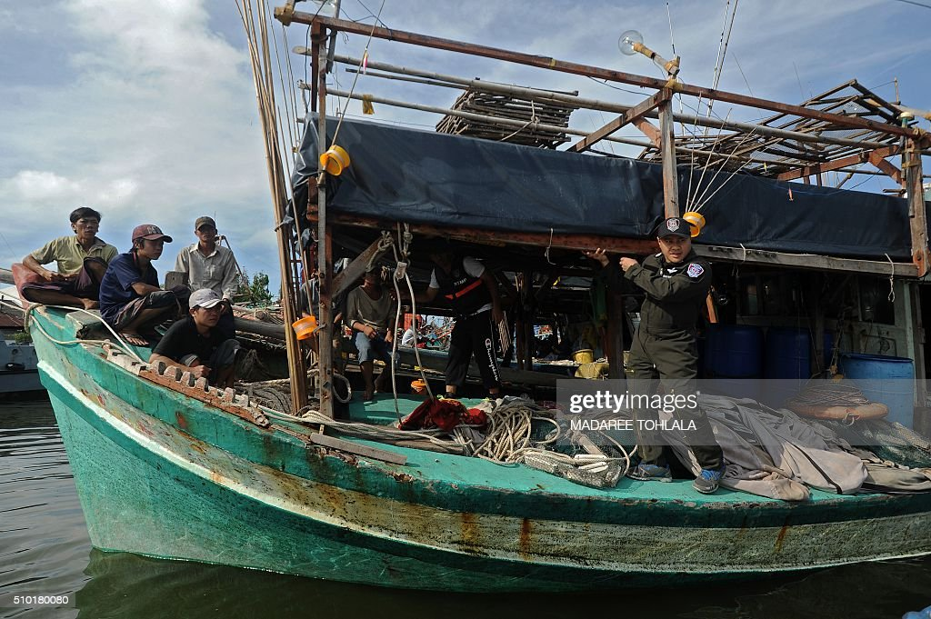 Vietnamese fishermen (L) sit on their seized boat after they were detained at sea by the Thai Royal Marine Police (R) in Thailand's province of Narathiwat on February 14, 2016. The Thai police said they arrested 31 Vietnamese fishermen off the coast of southern Narathiwat province for illegally fishing in Thai waters. AFP PHOTO / MADAREE TOHLALA / AFP / MADAREE TOHLALA
