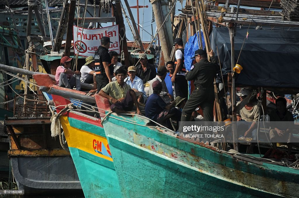 Vietnamese fishermen (L) sit on their seized boats after they were detained at sea by the Thai Royal Marine Police (R-standing) in Thailand's province of Narathiwat on February 14, 2016. The Thai police said they arrested 31 Vietnamese fishermen off the coast of southern Narathiwat province for illegally fishing in Thai waters. AFP PHOTO / MADAREE TOHLALA / AFP / MADAREE TOHLALA