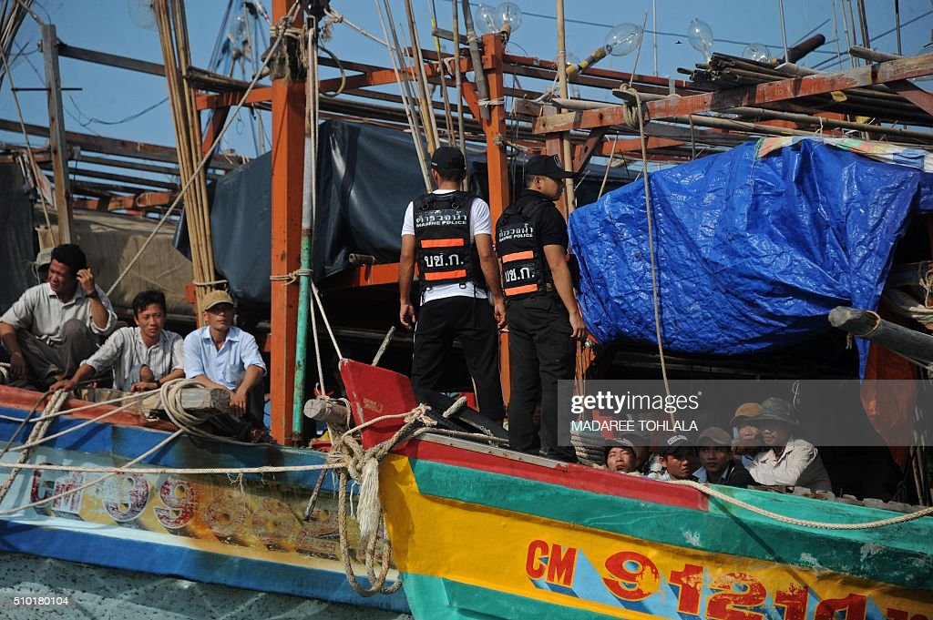 Vietnamese fishermen (L and R) sit on their seized boats after they were detained at sea by the Thai Royal Marine Police (C-standing) in Thailand's province of Narathiwat on February 14, 2016. The Thai police said they arrested 31 Vietnamese fishermen off the coast of southern Narathiwat province for illegally fishing in Thai waters. AFP PHOTO / MADAREE TOHLALA / AFP / MADAREE TOHLALA