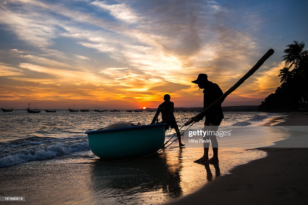 Vietnamese fishermen with traditional boat