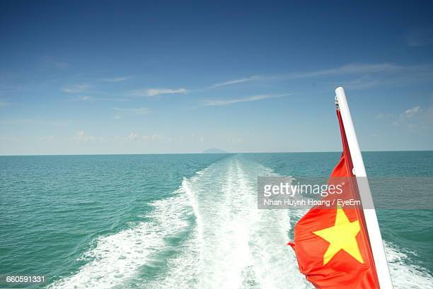 Vietnamese Flag In Sea Against Sky On Sunny Day