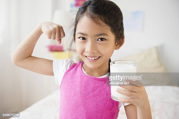 Vietnamese girl flexing muscles with glass of milk