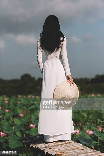 Vietnamese girl wearing Ao Dai (Long Dress) at Lotus pond