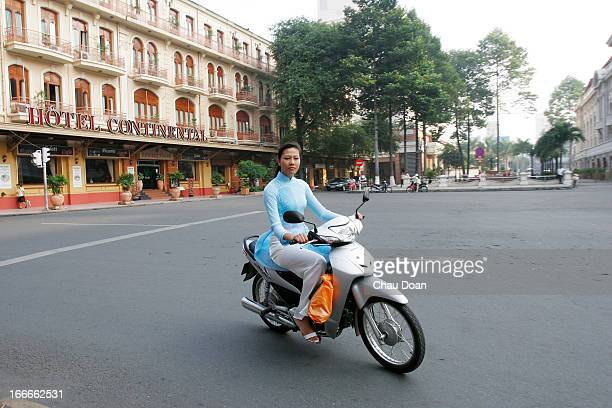 Vietnamese girl wearing the traditional Ao Dai rides past the Continental Hotel