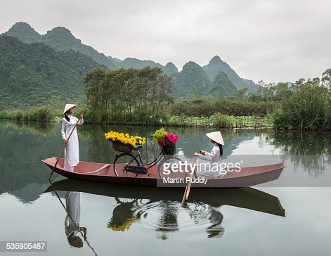 Vietnamese girls rowing boat along river