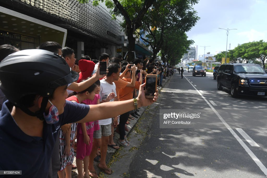 Vietnamese line the street as the convey transporting US President Donald Trump passes by, after his arrival for the Asia-Pacific Economic Cooperation (APEC) Summit in the central Vietnamese city of Danang on November 10, 2017. World leaders and senior business figures are gathering in the Vietnamese city of Danang this week for the annual 21-member APEC summit. Nam