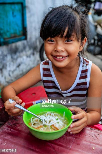 Vietnamese little girl eating a pho bo, South Vietnam