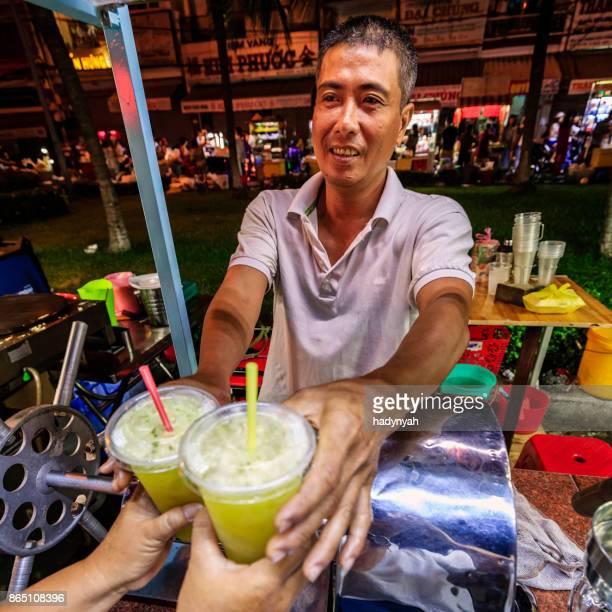 L'homme vietnamien vente jus de canne à sucre sur nuit marché, Delta du Mekong, Vietnam