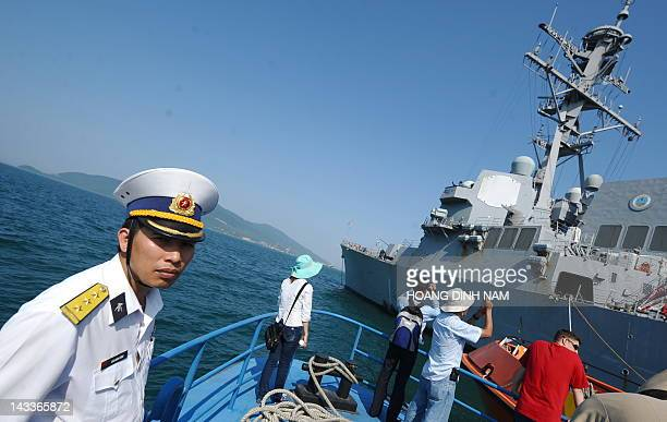 A Vietnamese navy's officer looks the guided missile destroyer USS Chafee as he leaves on a boat after attending a disaster control training with US...