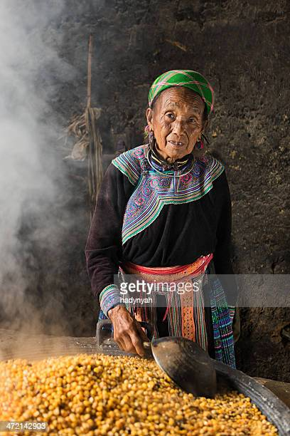 Vietnamese old woman from Flower Hmong Tribe preparing corn wine