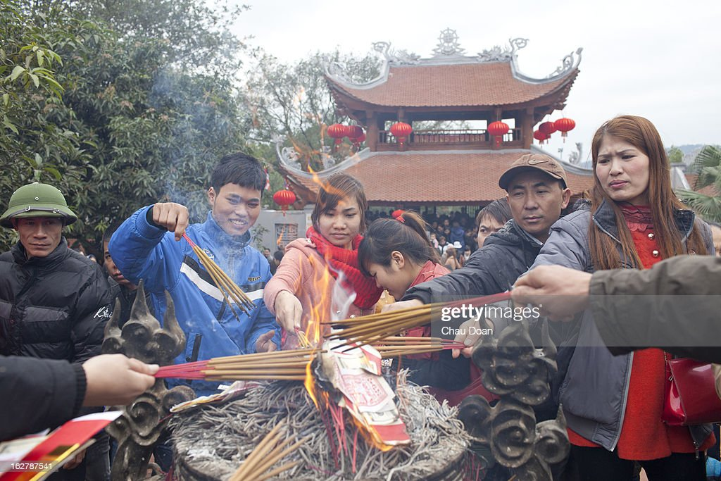 Vietnamese people light incense prior to entering a pagoda at the Lim festival. The Lim festival takes place at the 13th day of the first lunar month in Lim village, about 18 kilometers from Hanoi. This is one of the most well-known festivals in Vietnam when folk songs called Quan Ho are performed. The legend says that a woman named Ba Mu, who attained enlightenment after becoming a Buddhist monk at the Lim pagoda, had ended a drought in the village on the request of the villagers. Henceforth the people of the village worshipped her as their protector and took the date of her enlightenment as the date of the festival in Vietnam. Quan Ho is the dialog performance between male singers and female singers. The singers have to be quick witted and have strong grasp of traditional tunes, history and meaning of the songs..