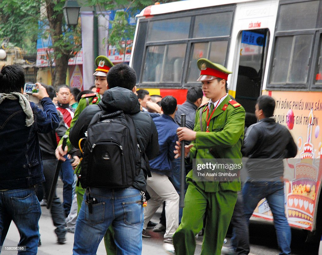 Vietnamese police officers forcely remove anti-China protesters marching on toward the Chinese Embassy on December 9, 2012 in Hanoi, Vietnam. Territorial tension heightens over the South China Sea as a Chinese vessel cut the cable of survey ship of the Vietnam's state-owned oil company at the end of November. 17 core members of the rally were arrested.
