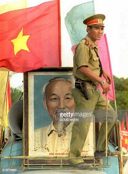 Vietnamese policeman waits on a float carrying a portrait of Ho Chi Minh before the start of a parade 29 April 1995 in Cu Chi Vietnam on the eve of...