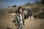 Vietnamese pop diva Hong Nhung fights back tears as she stands near the carcass of a decomposing white rhino on the banks of a river in the Kruger...