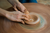 A Vietnamese potter uses a pottery wheel to fashion a piece of poetry from raw clay