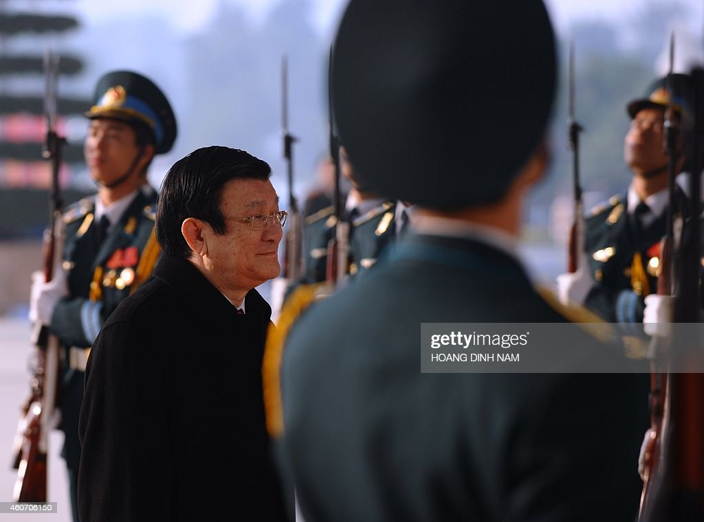 Vietnamese president Truong Tan Sang (2nd L) arrives at the National Convention Center to attend an official meeting marking the 70th anniversary of the Vietnam People's Army in Hanoi on December 20, 2014. The Vietnam People's Army (VPA) was founded on December 22, 1944. AFP PHOTO / HOANG DINH Nam