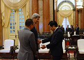 Vietnamese President Truong Tan Sang asks about the injured leg of the US Secretary of State John Kerry as they meet at the presidential palace in...