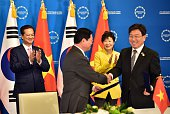 Vietnamese Prime Minister Nguyen Tan Dung and South Korean President Park GeunHye clap as South Korea's Trade Industry and Energy Minister Yoon...