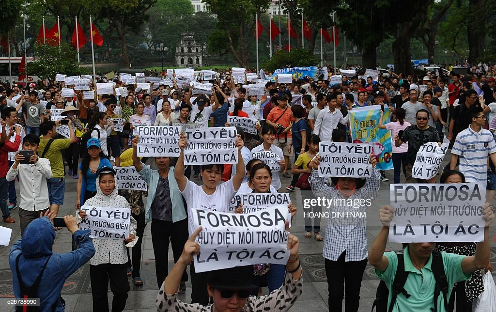 Vietnamese protesters demonstrate against Taiwanese conglomerate Formosa during a rally in downtown Hanoi on May 1, 2016. Around a thousand people poured into Vietnam's two major cities Hanoi and Ho Chi Minh City to protest against Taiwan's Formosa, which operates a steel plant which they claim is causing mass fish kills due to pollution in Vietnam's central coast. / AFP / HOANG