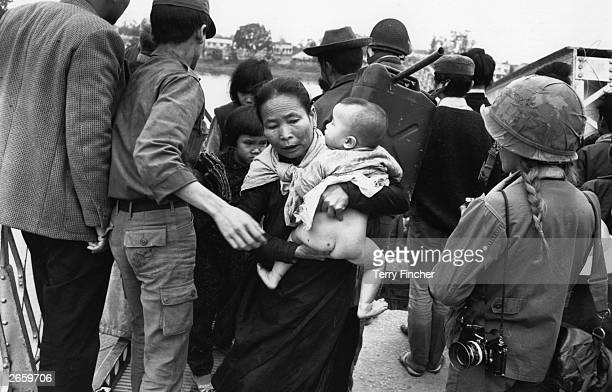 A Vietnamese refugee crossing the Perfume River with her child