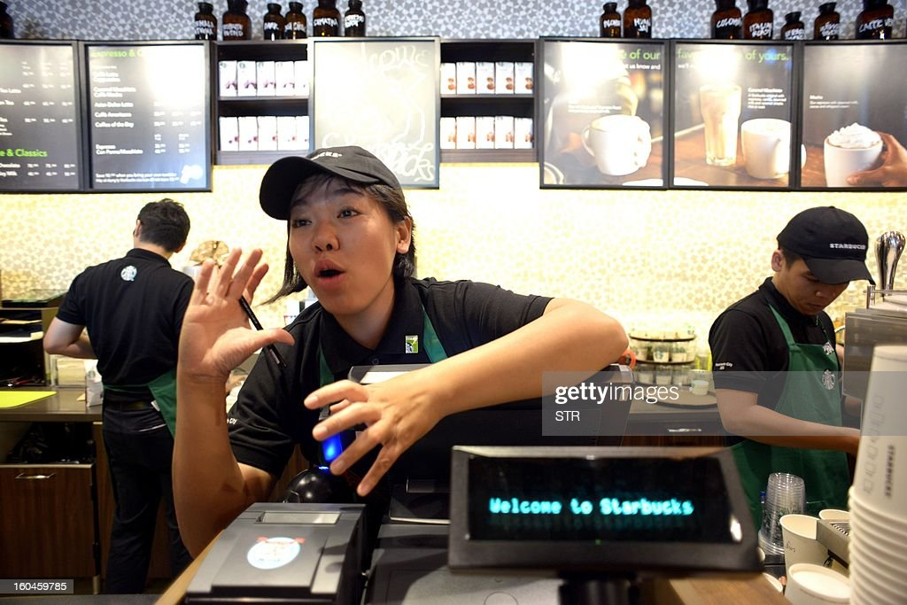 A Vietnamese Starbucks employee takes an order for a customer during the grand opening ceremony of the first Starbucks store in Vietnam, in Ho Chi Minh City on Feburary 1, 2013. Starbucks aims to have almost 4,000 stores in the Asia-Pacific by the end of 2013, including 1,000 in China.