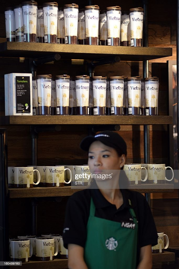 A Vietnamese Starbucks employee waits for customers during the opening ceremony of the first Starbucks store in Vietnam, in Ho Chi Minh City on Feburary 1, 2013. Starbucks aims to have almost 4,000 stores in the Asia-Pacific by the end of 2013, including 1,000 in China.