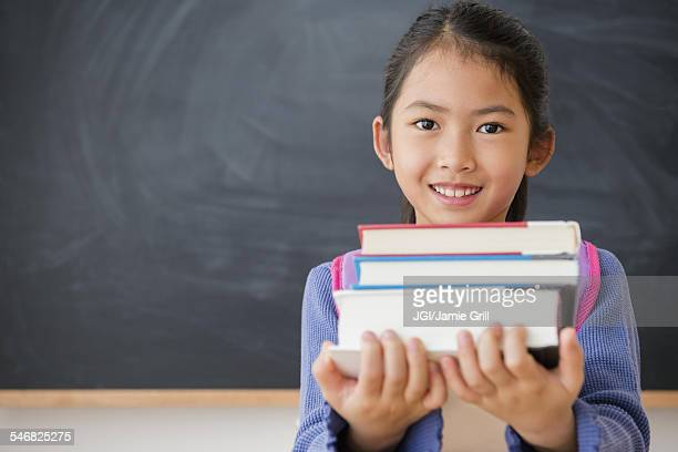 Vietnamese student carrying textbooks in classroom